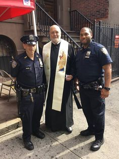 Paulist Fr. John Collins with two of New York's Finest! — at Holy Cross Church (New York City) on Sept 20, 2017.