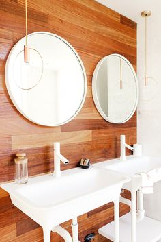 Wood bathroom with two sinks and round mirrors
