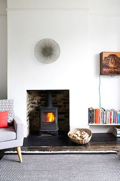 """""""I was determined not to fill the alcoves by the fireplace with bookshelves, like most people do,"""" Macnair says of her living room. """"I like odd shelves in unexpected places such as above doors or low New Living Room, Home And Living, Living Room Decor, Living Spaces, Contemporary Wood Burning Stoves, Fireplace Bookshelves, Fireplace Hearth, Empty Fireplace Ideas, Wood Burner Fireplace"""