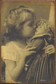 little girl kissing her doll