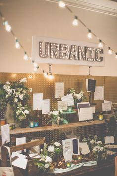 display inspiration: gold painted pegboard with rustic plank shelving, metal marquee light sign, colored votive glass, tree stump vases for florals {The Cream Event Los Angeles}
