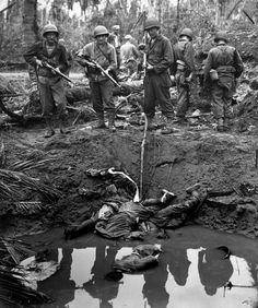 Three Japanese snipers elected to shoot it out during the battle for Leyte Island (1944). They were killed by U.S. Marines and fell into the muddy water of a bomb crater. Photographed by Harry R. Watson of the U.S. Coast Guard