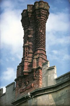 The chimneys at Thornbury in Gloucestershire, probably imitate those at Richmond Palace. This virtuosic triple-shafted example has miniaturised arrow loops and pinnacles. A scroll at the base is inscribed Richmond Palace, English Love, Burj Khalifa, Country Life, Medieval, England, Chivalry, Rooftops, Architecture
