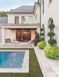 A covered patio equipped with RH outdoor furnishings ensures comfortable outdoor living. Tyson added topiary Ligustrums in garden boxes flanking the arched windows; trailing sweet potato vine creates a soft base plant for the topiaries in summer. Artificial turf surrounds the pool.