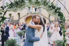 Married outside in Tuscany under a beautiful arch decorated with roses, Hydrangeas, gypsophila, eucalyptus and olive leaves -  Image by  Sara Lincoln Photography - Rime Arodaky gown for a Tuscany wedding with a white and grey colour scheme and bridesmaid dresses from ASOS.