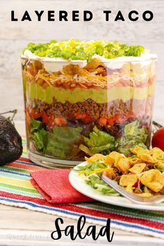 Layered Taco Salad takes the classic Taco salad that you love and then layers it in a fun trifle dish to create a beautiful presentation that is ready in minutes as it combines lettuce, beans, tomatoes, taco meat, guacamole, and cheese that is then topped with Salsa, green onion, sour cream, and Frito corn chips. Great Recipes, Favorite Recipes, Fall Recipes, Delicious Recipes, Recipe Ideas, Layered Taco Salads, Trifle Dish, Green Salsa, Good Food