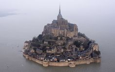 An aerial view as a high tide submerges a narrow causeway leading to the Mont Saint-Michel, on France's northern coast, Saturday, March 21, 2015.