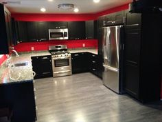"""Gray floors in the kitchen! """"Completely remodeled my kitchen. Moved a door which leads to my garage, and also moved a wall 2 feet to incorporate more cabinets and appliances. Also removed a closet and let the hardwood run all the way to the living room."""""""