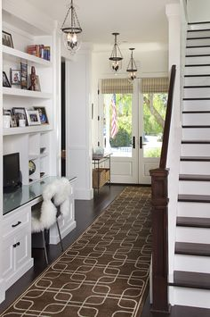 Lanterns, runner, glass panel front doors, white trim & built-ins, staircase w/ white risers and dark treads.
