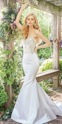 White silk faced duchess satin trumpet bridal gown with a strapless sweetheart neckline and encrusted jeweled natural waist bodice.