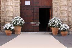 Vista general puerta de iglesia decorada con tinajas de barro y margaritas