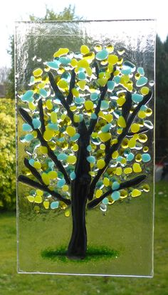 Yellow and Turquoise fused glass tree suncatcher. This is a very tactile design using transparent and opaque yellow and turquoise frit for the blossom of a tree fused on to clear glass. Green frit has been used at the bottom of the suncatcher and black glass for the trunk and branches of