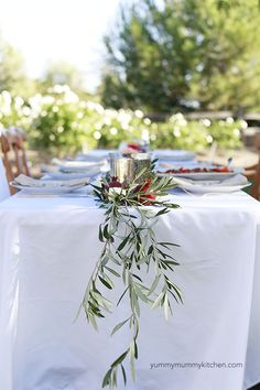 An olive branch runner + pomegranates and gold flatware make a pretty holiday table.