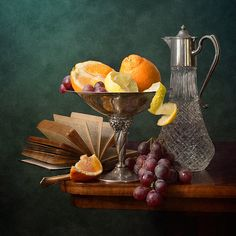 http://nikolay-panov.artistwebsites.com/products/oranges-and-grapes-nikolay-panov-art-print.html  • Fruit still life with fresh oranges and lemons in metal vase, and pink grapes, old book and tall glass pitcher on wooden table