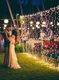Confira 10 ideias de iluminação para casamentos ao ar livre:. Noivos dançam em cerimônia de casamento rústico com luzes de natal ao fundo em um gramado verde durante festa.