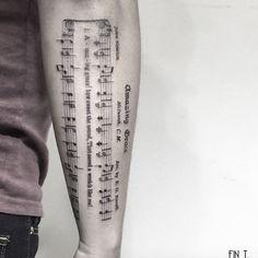 Sheet music tattoo by Fin Tattoos