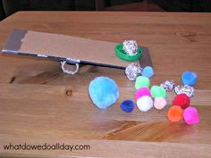 Kids will love playing indoors with this easy to make, simple, homemade catapult at home using duct tape and cardboard from the recycling bin.