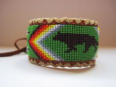 Native American Beaded Walking Wolf on Leather Cuff Bracelet looks great on both men and women.    Wolf Medicine - Guardian, Ritual, Loyalty, Spirit. Wolves are often misunderstood animals. In fact, they are friendly, social and highly intelligent. This beautiful wolf on green with 6 white feathers beaded cuff on brown leather was made with the smaller size 15 seed beads to show a sharper resolution. I first weaved it on the loom and then sew it onto double brown leather. All my own…