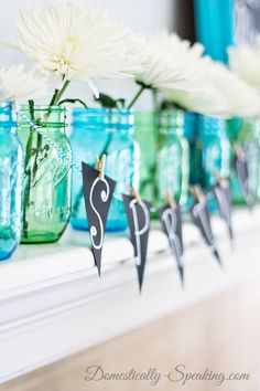 Spring Mason Jar Chalkboard Mantel - super cheery with blues and green and fun chalkboard art!  A beautiful dispaly for Easter that was simple to put together.  Love the chalkboard banner - it's a fun DIY project!