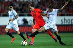 Ivan Rakitic (2ndL) of FC Barcelona competes for the ball with Grzegorz Krychowiak (R) of Sevilla FC during the La Liga match between Sevilla FC and FC Barcelona at Estadio Ramon Sanchez Pizjuan on April 11, 2015 in Seville, Spain.