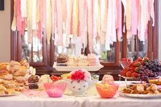Tea Party Birthday Idea. Cupcakes from Gigi's Cupcakes of Columbus. Teacups from TJ Maxx's clearance section. Teapots and stands from local thrift store. DIY sub sandwiches, PB sandwiches, Pigs in a Blanket, fruit, and veggies! DIY fabric streamers in background, 99 cent fabric squares from Hobby Lobby's handkerchief section. Buttons for table confetti. A paper mache number spraypainted to accent the centerpiece cupcakes.