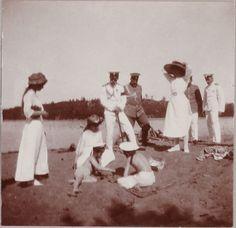 Grand Duchesses Olga Nikolaevna, Tatiana Nikolaevna e Maria Nikolaevna juntamente com Tsar Nicholas II (Nicolau II) e outros officers observam o Tsarevich Alexei Nikolaevich a se divertir na areia da praia da Finland com um amigo em 1911.