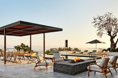 On the terrace of a Los Angeles home conceived by designer Dan Fink and architect Tim Murphy, Summit Furniture armchairs surround the fire pit, while the firm's chaise longues are positioned near the pool, shaded by a Janus et Cie umbrella; the dining table and chairs are by Dedon, and in the background is a totemic John McCracken sculpture.