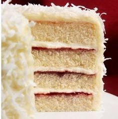A layer cake cut open to see the insides of jam and coconut