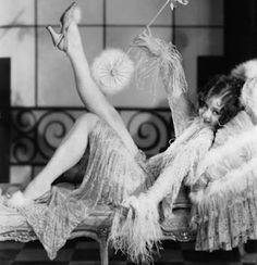 """Flapper in the 1920s was a term applied to a """"new breed"""" of young Western women who wore short skirts, bobbed their hair, listened to jazz, and flaunted their disdain for what was then considered acceptable behavior. Flappers were seen as brash for wearing excessive makeup, drinking, treating sex in a casual manner, smoking, driving automobiles and otherwise flouting social and sexual norms."""