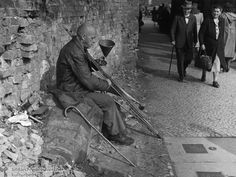 "Disabled Veteran as Street Musician (1945)  Entitled ""Musical Eccentric,"" this photograph shows a disabled veteran who attempts to earn money by playing music on a Berlin street corner.  Berlin, 1945."