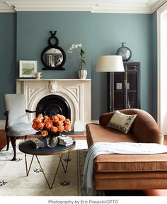 Muted teal walls with an orange velvet chaise.