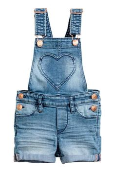 Bib overall shorts in washed stretch denim. Adjustable suspenders with metal fasteners, heart-shaped bib pocket with embroidery, and snap Denim Overall Shorts, Denim Dungaree Shorts, Denim Overalls, Short Overalls, Salopette Short Jean, Salopette Jeans, Short Court, Baby Jeans, Embroidered Shorts