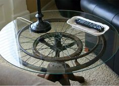 WHEEL TABLE.  Antique lovers, this one's for you. An old wheelchair wheel and stool were repurposed to function as the base of this one-of-a-kind industrial end table. The aged patina of the wheel peeks through the glass table top, adding further vintage charm to the piece. Editors' Favorite DIYs of 2014