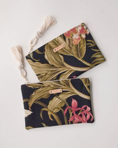 A modern zipper pouch thats great for holding all the accessories you dont want to loose track of in a larger bag. Its also cute on its own as a little clutch or makeup bag. This moody tropical floral is new for this year and Im in love. Its a gorgeous bundle of exotic leaves, flowers and the occasional insect, all in deep muted tones. This zipper pouch is perfect to keep around for all the extras - lipgloss, phone, etc. It keeps things much more secure and makes it easy to find them all in…
