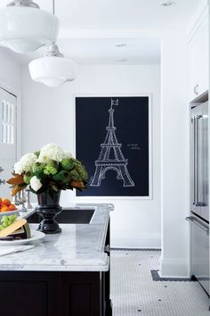 crisp, clean, and classic.  Love the schoolhouse lighting, marlbe counter tops, fresh flowers, black and white hexagon floor tile, and framed chalkboard eiffel tower sketch.