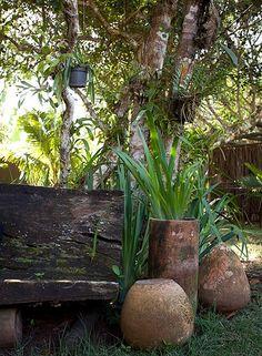 No jardim da casa da empresária Karin Farah, em Trancoso, o banco feito com tronco de madeira é acompanhado por vasos bem rústicos