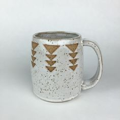 """stoneware mug in speckled brown stoneware with white glaze and descending triangle surface design. 3.75"""" height x 2.75"""" across. 4.5"""" wide including handle. all materials used are food safe. due to the unique surface textures of my work, handwashing is recommended."""