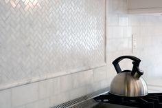 Marble Backsplash with herringbone mosaic feature. Cross stone has this not as much gray cleaner white