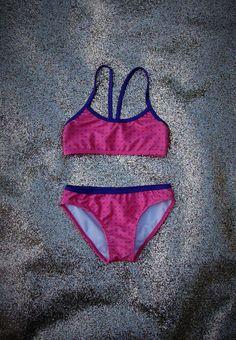 Bikini de niña. Top con vivo a contratono en escote y breteles, que van al centro de espalda. Vedetina alta con vivo a contratono en cintura. Combinación  Rosa-violeta, Azul-frutilla. T2-T14