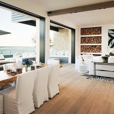 A relaxed beach house living, dining room and terrace overlooking the ocean. Gorgeous white, light brown and navy color scheme.