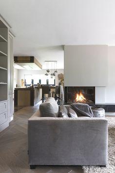 """De inbouwhaard geeft veel sfeer aan het interieur. De vloer is een dubbel gerookte eiken parket in visgraat gelegd. De keuken is op maat gemaakt. De eikenhouten keukenkasten worden gecombineerd met een marmeren blad. De barkrukken zijn in verschillend materiaal, wat zorgt voor een speels effect. Foto: Anneke Gambon – """"Stijlvol Wonen"""" - © Sanoma Regional Belgium N.V. Living Room Colors, Living Room Grey, Home Living Room, Living Room Designs, Living Room Decor, Modern Rustic Homes, Modern Interior Design, Small Living, Style At Home"""