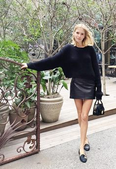 Russian style icon Lena Perminova goes full-on black and H&M. Black H&M sweater, faux leather mini skirt, and loafers. | H&M OOTD