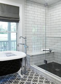 Beautifully designed two-toned gray and black bathroom boasts a polished nickel tub filler fixed to white and black mosaic fleur de lis floor tiles beside a black and white freestanding clawfoot tub placed in front of a window dressed in a charcoal gray roman shade.