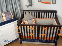 Grey crib bumper and dust ruffle with orange trim