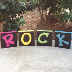 "Four small canvases spray painted with bright colors, stenciled letters on top and sprayed with black paint for my ""rockstar"" theme."