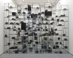 Terence Koh, Crackhead, 2006, 222 heads of plaster, paint, wax, fire, charcoal, inside 22 glass vitrines, UV glue, paint, fingerprints, some vitrines with breaks and/or cracks