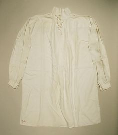 """1790s or later Shirt. One fabric covered wire button is at the bosom slit which otherwise laces. Buttons on wristband cannot be seen but are likely set to take sleeve buttons since the left sleeve shows a button whole on the bottom. This shirt is labeled """"O R"""" with a one below in red. Accession Number: 2006.132 at the MET"""