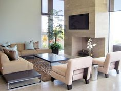 A sleek fireplace surround houses a flat-screen TV and serves as the focal point for this living room. A neutral sectional and two matching chairs frame the space, and a low coffee table and end tables accent the room's streamlined design. Large picture windows highlight the high ceiling and provide natural light throughout.