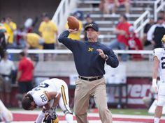 Michigan head coach Jim Harbaugh throws the ball during