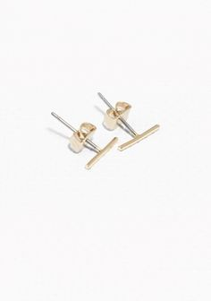 Simple and discreet, these thin bar studs are made from shiny brass.